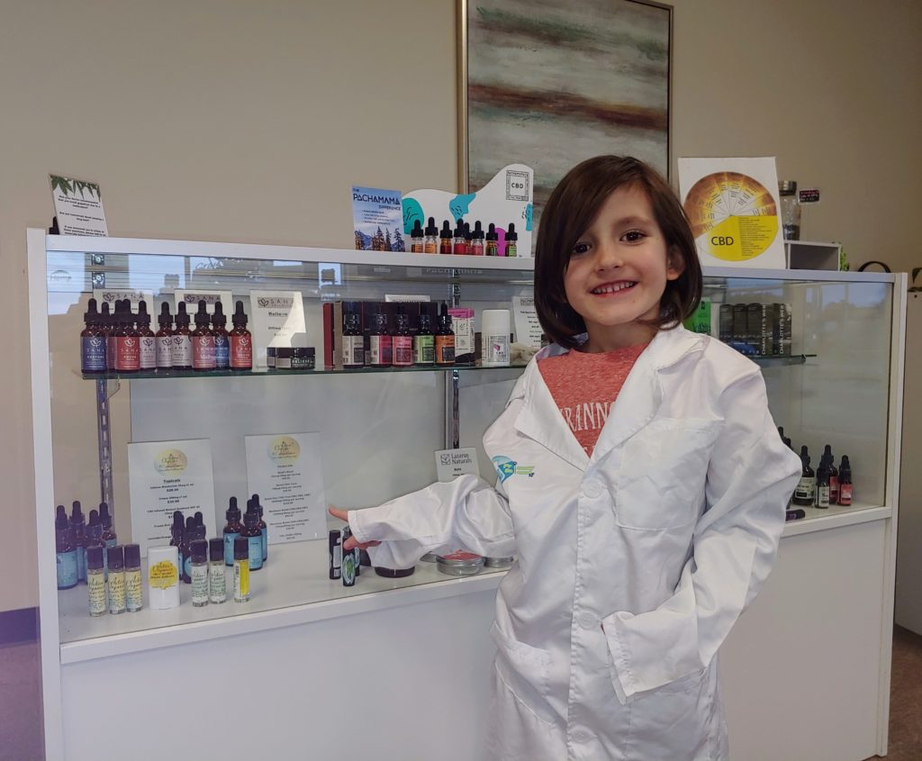 Child in lab coat surrounded by CBD bottles